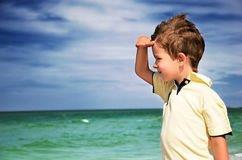 boy-looking-away-his-palm-background-cloudy-sky-sea-horizontal-42859858